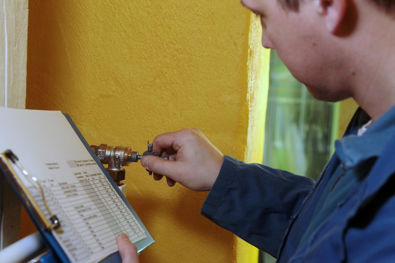 Ein SHK-Handwerker stellt ein voreinstellbares Thermostatventil ein. (Quelle: co2online/Alois Müller)
